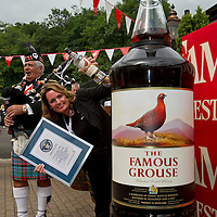 12.8.2012. Its a record winner.... The largest bottle of whisky in the world is now to be found in Crieff at the Famous Grouse Experience (FGE). In total 228 Ltr bottles of whisky were used to fill the giant bottle, with a street price of around £4500.<br /> Tracy McCafferty, the General Manager of the FGE holds the Guinness certificate and one of the empty 1ltr bottles used to take the title from the previous largest bottle of Jack Daniels. COPYRIGHT: Perthshire Picture Agency.<br /> Tel. 01738 623350 / 07775 852112.