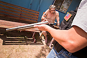 21 SEPTEMBER 2010 - PHOENIX, AZ: Phoenix detective Shane Forbes (CQ RIGHT WITH FLAG PATCH) holds a sawed off shotgun while he talks to Phillip Parks (CQ BY PD) allegedly a member of Hell's Angels and allegedly the owner of the shotgun. Parks was arrested for possessing a prohibited weapon because the barrel of the shotgun was less than 18 inches long. Crime has steadily dropped in Phoenix over the past few years, in line with national trends. The latest number released this month showed Phoenix reported fewer 2010 homicides, rapes, robberies, thefts - in addition to other major crimes -- compared with the same time period the previous year. Detectives in the Phoenix police department's Major Offender Unit make several arrests every day.  PHOTO BY JACK KURTZ