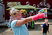 The oldest girl in the Little Miss Chauncey pageant, Hannah Lanning fires a bubble-gun to amuse her step-brother Leum, 4, during the New Straightsville Moonshine Festival, on Saturday afternoon, May 23.