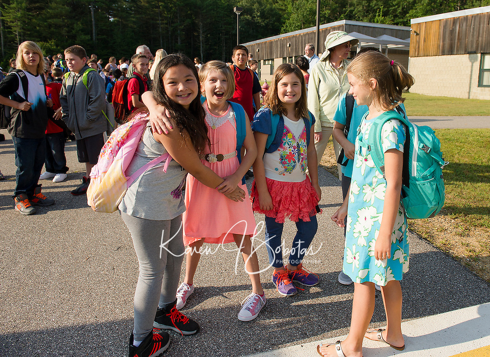 Keirah Sanborn, Zaria Ainsworth, Phoebe Townsend and Mia Lynch gather outside of Woodland Heights Elementary before going inside to start their first day of 5th grade Monday morning.  (Karen Bobotas/for the Laconia Daily Sun)