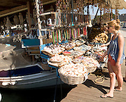 Shells on sale girl shopping Rhodes town, Rhodes, Greece