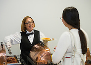 A food services employee serves guests at reception following opening ceremony at The Rusk School, April 7, 2014.