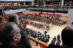 © Licensed to London News Pictures. 26/10/2014<br />  One minute silence today at Bluewater.<br /> Bluewater joins forces with the Royal British Legion to remember In the year that marks 100 years since the birth of the poppy as a symbol of Remembrance and hope, Bluewater is supporting the Royal British Legion's Poppy Appeal campaign with a two-week mall takeover, beginning with the formal launch of the Poppy Appeal in Kent. The 26th October has seen an external parade of 150 people, including standard bearers, veterans, serving personnel, reserves, cadets, Scouts and Brownies joining the Royal British Legion in a procession around Bluewater. Also attending the parade will be Gareth Johnson, MP for Dartford, Councillor Avtar Sandhu MBE, the Mayor of Dartford, and Councillor John Caller, the Mayor of Gravesham. Concluding the launch of the Poppy Appeal at 12:20pm will be a performance by Gareth Malone's Military Wives Choir, from Brompton Barracks in Chatham. The Military Wives will sing in Bluewater's Plaza (outside Glow) before the Royal British Legion leads a spoken tribute and minute's silence. From then until 11th November, when there will be a Remembrance Day memorial silence, the Royal British legion will be stationed at an in-mall collection point on the lower Thames Walk fundraising for the charity.<br /> <br /> (Byline:Grant Falvey/LNP)