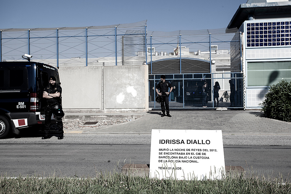 """The Mossos d'Esquadra - the police force of Catalonia, stand  by the entrance of the CIE with in front,  a cartel denouncing the death of Idrissa Diallo who died on 6 January 2012 while being under custody in the CIE of Barcelona.  Protest organized by """"Tancarem el CIE"""" - Barcelona  20/06/2015"""
