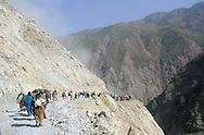 Earthquake refugees carry aid on their backs across a landslide and into the Neelum Valley, November 9, 2005, Muzaffarabad, Pakistan. The South Asia earthquake measured 7.6 on the Richter Scale in Pakistan Administered Kashmir just before 9am on Saturday, October 8, 2005 and is the twelfth most destructive earthquake in recorded history, killing 87,000 and internally displacing 3 million. Early assessments indicate it will take upwards of 10 years for the affected regions to fully recover from the damage, however, scientists estimate the region should prepare for future earthquakes on a much larger scale, citing the Eurasian and Indian tectonic plates running through Kashmir as extremely  unstable. (Photo by Warrick Page)