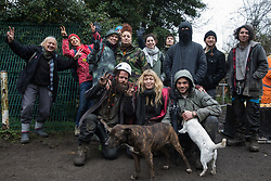 Harefield, UK. 13 January, 2020. Stop HS2 activists pose alongside a gate being erected by a team of engineers and enforcement agents across a public right of way leading to a protection camp. Part of the nearby Colne Valley protection camp was evicted by bailiffs last week. 108 ancient woodlands are set to be destroyed by the high-speed rail link and further destruction of trees for HS2 in the Harvil Road area is believed to be imminent.