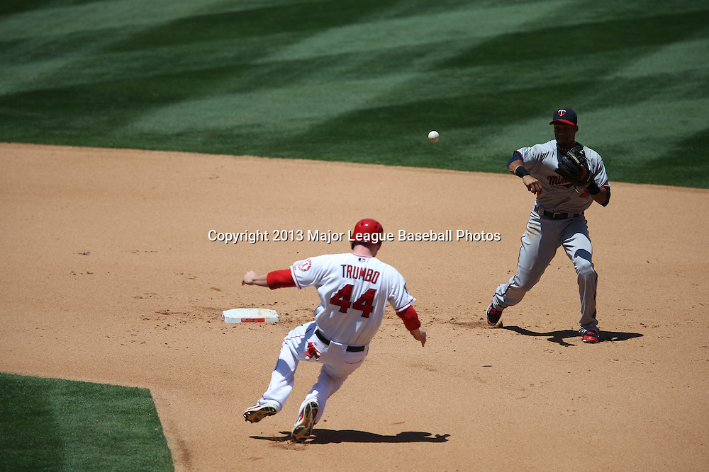 ANAHEIM, CA - JULY 24:  Mark Trumbo #44 of the Los Angeles Angels of Anaheim gets forced out at second base by Pedro Florimon #25 of the Minnesota Twins who throws to first base to complete a double play while during the game against the Minnesota Twins on Wednesday, July 24, 2013 at Angel Stadium in Anaheim, California. The Angels won the game in a 1-0 shutout. (Photo by Paul Spinelli/MLB Photos via Getty Images) *** Local Caption *** Mark Trumbo;Pedro Florimon