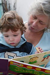 Portrait of a woman reading to a little boy,