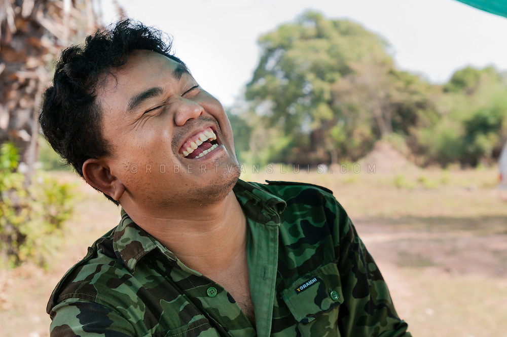 Aki Ra, former Khmer Rouge child soldier, bursts out laughing during an interview in Cambodia