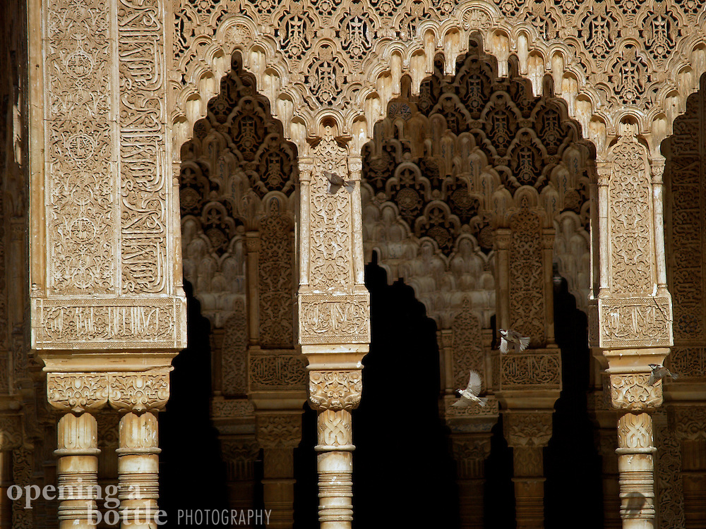 Sparrows take flight in front of the ornately carved arcades of the Courtyard of Lions, inside the Palacios Nazaries of the Alhambra, Granada (Andalusia), Spain.