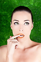 Closeup portrait of a beautiful nervous woman biting her finger while looking up isolated on green
