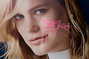 Pink graffiti tag scrawled over the face of a model, appearing on a central London fashion poster.