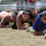 Stephanie Dextraze, (centre), in action at the barbed wire crawl obstacle during the Reebok Spartan Race. Mohegan Sun, Uncasville, Connecticut, USA. 28th June 2014. Photo Tim Clayton