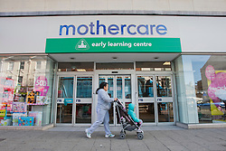 © licensed to London News Pictures. London, UK 12/04/2012. A mother with her child waiting outside Mothercare before the shop opens this morning in Wood Green (12/04/12). Mothercare expected to be shutting 111 stores with 700 job losses. Photo credit: Tolga Akmen/LNP