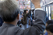 graying middle aged businessman standing in a Tokyo subway