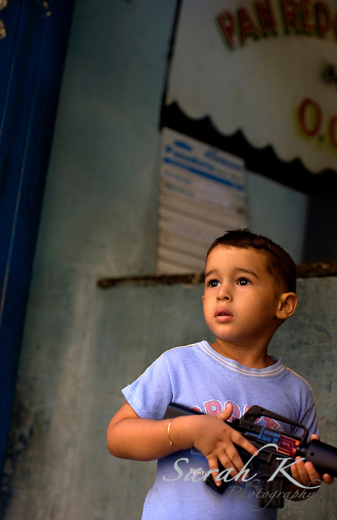 A young boy armed with a toy gun in Havana, Cuba, waits for his mother to purchase bread using a ration card.