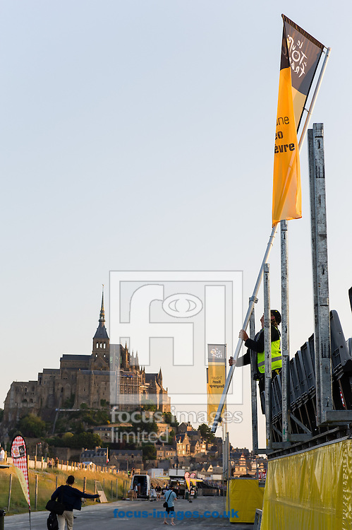 Picture by Andrew McLean Brown/Focus Images Ltd + 33 670 67 8592<br /> 10/07/2013<br /> Just before 7.00am a worker installs flags at the Arriv&eacute;e of stage 11 of the Tour de France, Avranches to Mont-Saint-Michel, France.