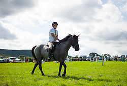 © Licensed to London News Pictures.12/08/15<br /> Danby, UK. <br /> <br /> A woman rides her horse out into the main arena to compete in an event during the 155th Danby Agricultural Show in the Esk Valley in North Yorkshire. <br /> <br /> The popular agricultural show attracts competitors and visitors from all over the surrounding area to this annual showcase of country life. <br /> <br /> Photo credit : Ian Forsyth/LNP