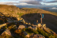 A mountain hiker and his dog at sunrise overlooking Coire an t-Sneachda in the Cairngorms National Park, Scotland.