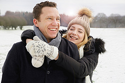 Smiling Father and Daughter in Snowy Field
