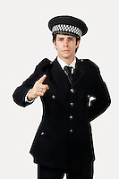 Portrait of confident police officer gesturing against gray background