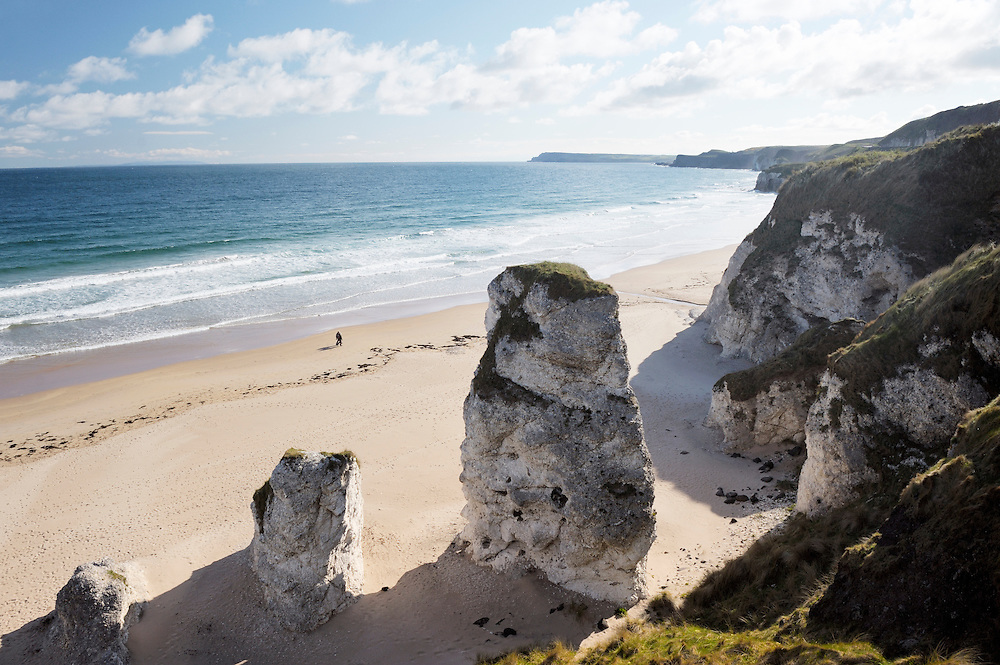 Couple walking alone on beach at the White Rocks between Portrush and Bushmills, Northern Ireland. Eroded limestone cliffs