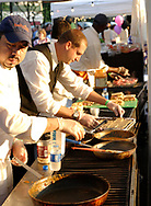 Folks in the Bellyfire catering booth get some 'golden light' from the setting sun as they prepare samples during the 21st annual The Taste in the Lincoln Park Commons area at the Fraze Pavilion, Thursday, September 3, 2009.