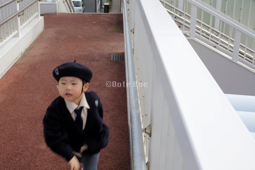 preschool child in uniform running home Japan