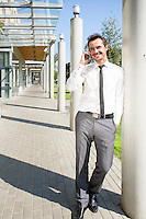 Young businessman using cell phone while leaning on column outside office
