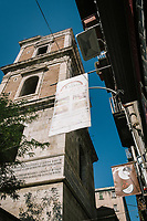 "NAPLES, ITALY - 10 OCTOBER 2018: A banner of La Taverna a Santa Chiara is seen here by the campanile (bell tower) of the Monastery of Santa Chiara , in the historical center of Naples, Italy, on October 10th 2018.<br /> <br /> The idea of the founders Nives Monda and Potito Izzo (two really unusual names in southern Italy) was to create a ""taste gate"" of Campania products. La Taverna a Santa Chiara, founded in 2013, is a modern tavern whose strengths are the choice of regional and seasonal products and mostly small producers. Small restaurant, small producers.<br /> The two partners tried to put producers and consumers in direct contact, skipping the distribution, and managing to reduce the costs of the products considerably. Nives and Potito managed to create a simple kitchen, at moderate costs but with high quality raw materials.<br /> ""A different restaurant idea,"" says Nives, ""the producers deliver their products at low prices and the tavern manages to make traditional dishes with niche products"".<br /> Nives Monda has been a labor consultant for 20 years. Potito Izzo is the chef who has always been loyal to the  family cuisine. When he embraced the idea of Nives he found in the tavern the natural place to express the tradition of Neapolitan cuisine. Nives defines him as a ""comfort food chef"". Their partnership is a true friendship that has lasted for over 10 years."
