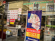22 APRIL 2013 - BANGKOK, THAILAND:    The exchange rate is posted in the window of a tourist curio shop that also operates as a currency exchange in Bangkok. The Thai Baht has gained markedly against the US Dollar, the Euro and Pound Sterling in recent months. On Monday, the Baht was trading at 28.57 Baht to 1 US Dollar on Apr. 22. The strengthening Baht means imported goods are cheaper in Thailand, but Thai exports cost more in other countries. It also means tourists and expats who live in Thailand have less money to spend as their currencies buy fewer Baht. The baht has risen 5 percent against the dollar this year to its highest level since before the Asian financial crisis in 1997. The Federation of Thai Industries, which has led calls for the authorities to act to lower the baht, said the rise in the past two weeks had been too rapid and its members were finding it hard to cope with the volatility because as the Baht appreciates their exports become more expensive. Thailand is among the world's leading exporters of rice, chicken, pork, electrical components, cars and is the leading exporter of canned tuna. PHOTO BY JACK KURTZ
