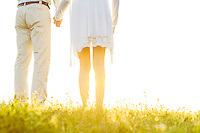 Midsection back view of couple holding hands on grass against sky