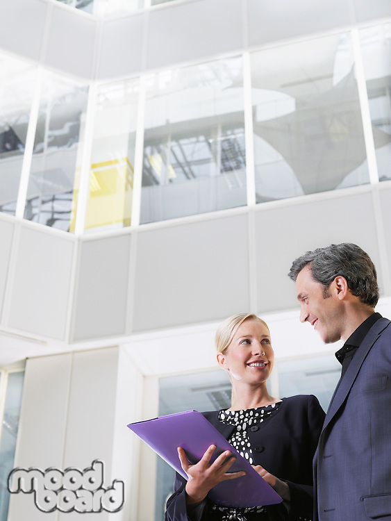 Two business people smiling holding paper folder low angle view