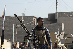 Licensed to London News Pictures. 11/11/2016. Mosul, Iraq. An Iraqi Police office mans a DShK heavy machine gun mounted on a pickup truck as soldiers of the Iraqi Army's 9th Armored Division visit Mosul's Al Inisar district on the south east of the city. The Al Intisar district was taken four days ago by Iraqi Security Forces (ISF) and, despite its proximity to ongoing fighting between ISF and ISIS militants, many residents still live in the settlement without regular power and water and with dwindling food supplies.<br /> <br /> The battle to retake Mosul, which fell June 2014, started on the 16th of October 2016 with Iraqi Security Forces eventually reaching the city on the 1st of November. Since then elements of the Iraq Army and Police have succeeded in pushing into the city and retaking several neighbourhoods allowing civilians living there to be evacuated - though many more remain trapped within Mosul.  Photo credit: Matt Cetti-Roberts/LNP