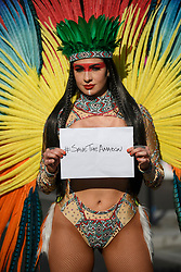 © Licensed to London News Pictures. 26/08/2019. London, UK. A woman in carnival dress poses with a sign reading #SAVETHEAMAZON at day two of the Notting Hill carnival. The two day event is the second largest street festival in the world after the Rio Carnival in Brazil, attracting over 1 million people to the streets of West London. Photo credit: Ben Cawthra/LNP