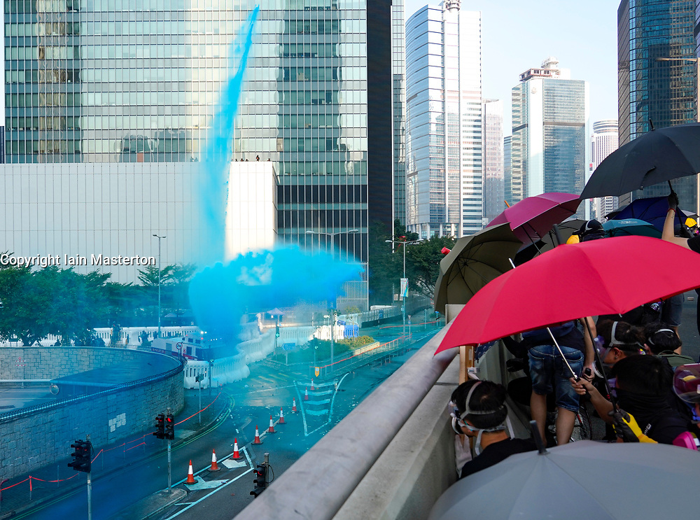 Hong Kong. 1 October 2019. After a peaceful march through Hong Kong Island by an estimated 100,000 pro democracy supporters, violent flared up at Tamar, Admiralty and moved through Wanchai district. Police used teargas and baton rounds and water cannon. Hard core group lit fires, threw bricks and Molotov cocktails at police. Violence continues into evening. Protestors shelter from police water cannon.  Iain Masterton/Alamy Live News.