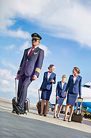 Portrait of mature pilot walking with three young beautiful flight attendants against airplane in airport