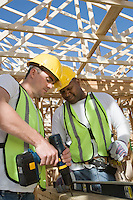 Two construction workers drilling on site