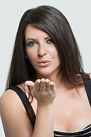 Portrait of beautiful young woman blowing kisses over gray background