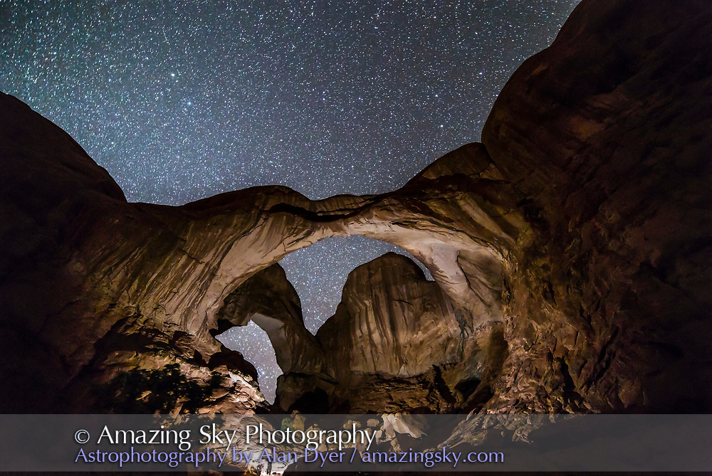 A photographer using a bright light to illuminate Double Arch in Arches National Park, Utah, on a dark night before moonrise provided natural illumination. Using bright lights to paint landscapes at night is common but often produces an artificial style of illumination.<br />