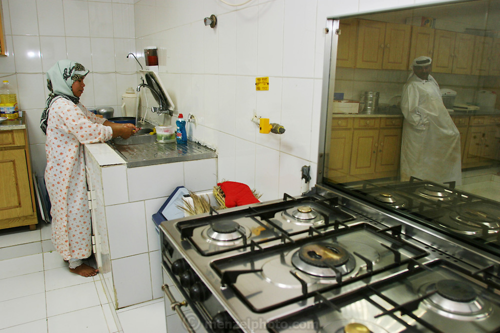 A Muslim guest worker servant from Indonesia washes the dishes in her employers' large modern kitchen in Dubai as the master of the house looks on. (Supporting image from the project Hungry Planet: What the World Eats). As an indigenous citizen of the United Arab Emirates this family is entitled to a substantial subsidy from the government and jobs for the males in the household. Their high standard of living is a far cry from his parents' life as nomadic Bedouin camel herders of the desert. Dubai, United Arab Emirates.