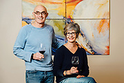 Rick Small and Darcey Fugman Small of Woodward Canyon with their wine and standing in front of a painting used for an Artist Series Label.