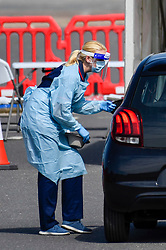 © Licensed to London News Pictures. 26/04/2020. WATFORD, UK. A worker in personal protection equipment (PPE) greets a car driver in a test centre which opened in the car park of Watford General Hospital on 23 April.  Those eligible to use the test centre are hospital staff members or their household who are symptomatic of Covid 19.  To accelerate the testing programme towards a target of 100,000 tests per day by 30 April set by Matt Hancock, Health Secretary, many more testing centre have been set up in the last few days including mobile pop-up test centres. Photo credit: Stephen Chung/LNP