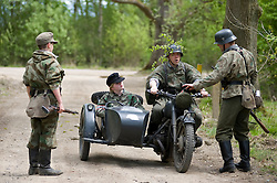 Reenactors from Northern World War Two Association, portraying elements of the elite Grossdeutschland division with a motorcycle and sidecar combinatione take part in a 24hr private exercise, held at Sutton Grange, near Ripon in Yorkshire. The white steel helmet or Stahlhelm marked on the front of the sidecar is the Großdeutschland Division tactical symbol, <br />