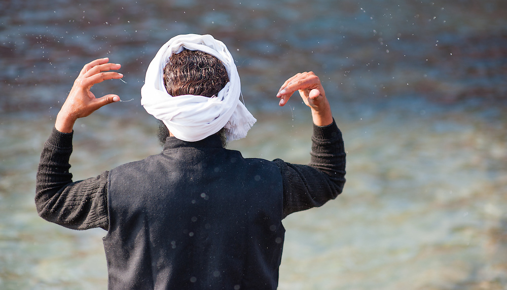 Indian man splashing water over his head by the Ganges in Haridwar (India)