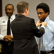 Richard McTear faces attorney Rocky Brancato as Brancato assists McTear with his necktie during the first day of jury selection in McTear's murder case Monday, July 14, 2014 in Tampa.
