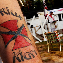 Kyle Green | The Roanoke Times<br /> 7/2/2011 A member of the Rebel Brigade KKK group in Martinsville, Virginia shows off a KKK tattoo before one of six cross burnings held on rural land in southwest Virginia. The KKK is making a comeback in the USA helped by high unemployment and a growing distrust in the government.