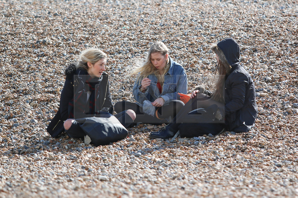 © Licensed to London News Pictures. 03/03/2015. Brighton, UK. A group of friends on Brighton beach relaxing in the first few sunny days of Spring 2015. Photo credit : Hugo Michiels/LNP