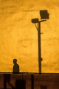 Shadow of man with golden sunset lit wall, Taunggyi