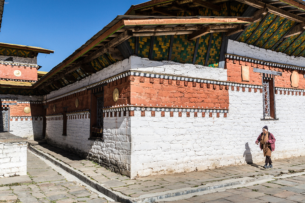 A man in circles an old temple in prayer. <br /> Bhumtang, Bhutan.